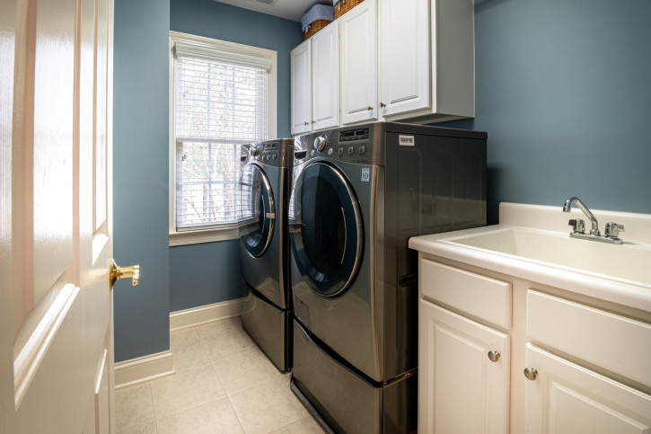 front load washing machine beside white window blinds