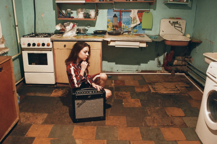 girl sitting beside gray and black fender guitar amplifier inside room