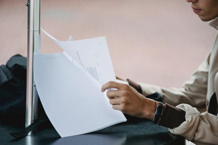 male student reading documents for homework task
