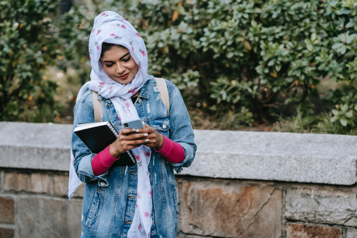 smiling ethnic woman messaging via contemporary cellphone near stone fence