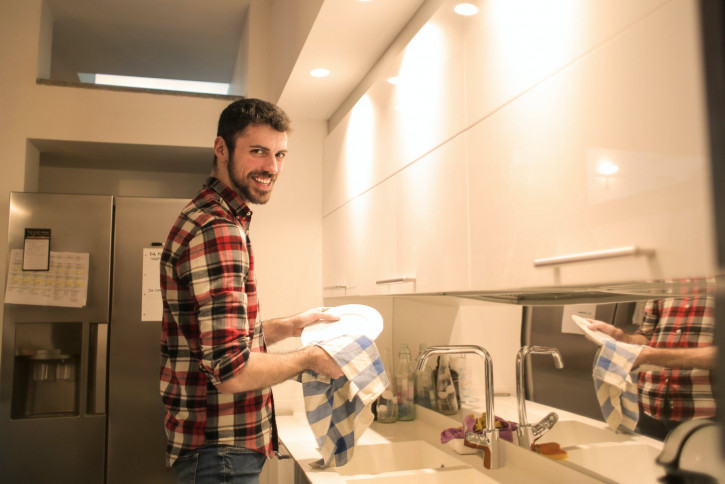 photo of a man washing dish plates