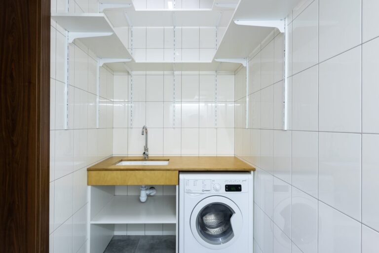 laundry area with white tiled walls