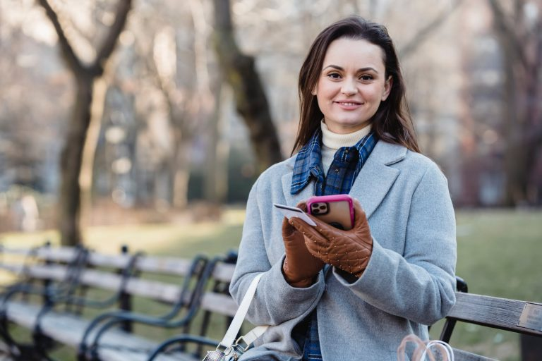 smiling woman using smartphone on spring city park