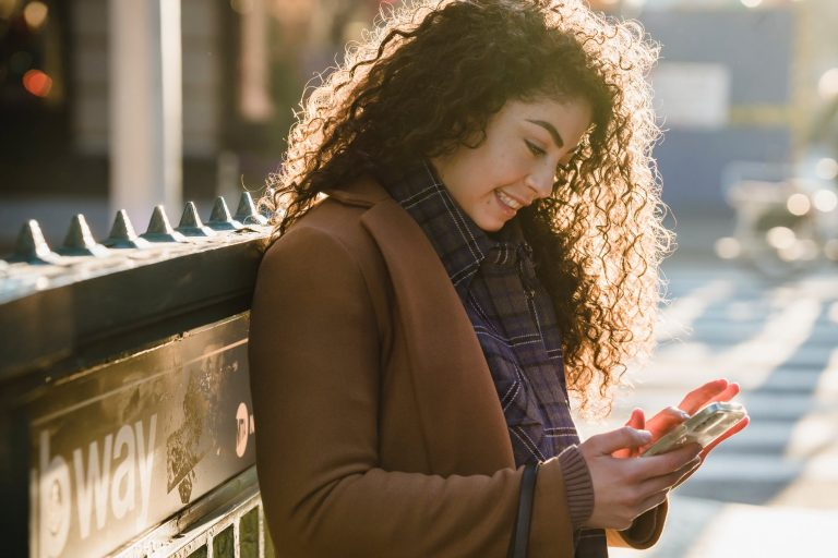 tensed woman texting message outdoors near cafe